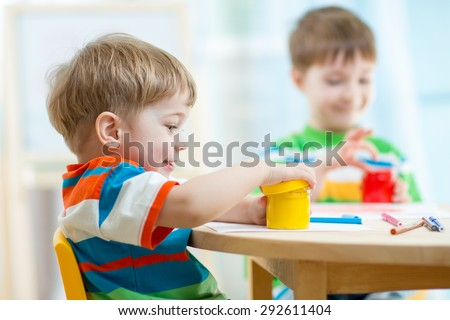 children play and paint at home or kindergarten or playschool or daycare - stock photo