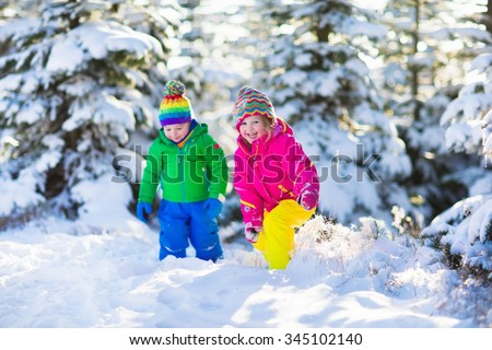 Children play in snowy forest. Toddler kids outdoors in winter. Friends playing in snow. Christmas vacation for family with young children. Little girl and boy in colorful jacket and knitted hat. - stock photo