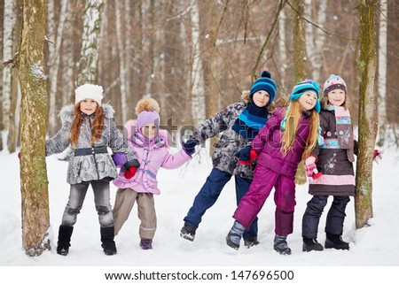 Children play in winter park tugging hands between two trees - stock photo