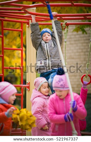 children play on the playground outside. A group of children playing together in kindergarten outside