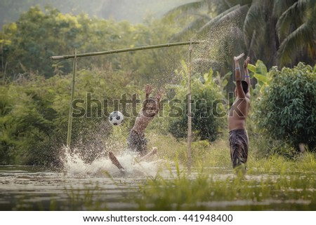 Children play soccer in the river