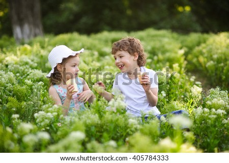 Children play together in the garden, eat ice cream and smile