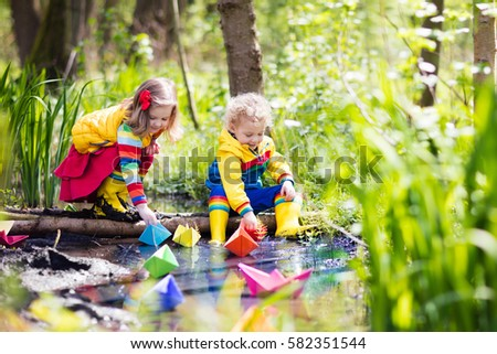 Children play with colorful paper boats in a small river on a sunny spring day. Kids playing exploring the nature. Brother, sister having fun at a forest stream. Boy and girl with toy boat and ship