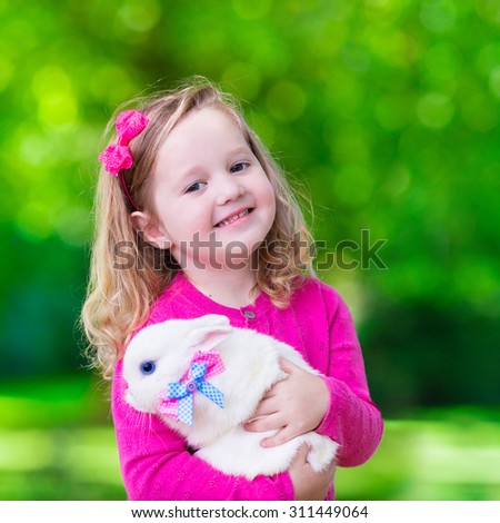 Children play with real rabbit. Laughing child at Easter egg hunt with white pet bunny. Little toddler girl playing with animal in the garden. Summer outdoor fun for kids with pets. - stock photo