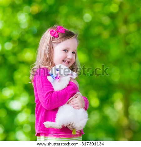 Children play with real rabbit. Laughing child at Easter egg hunt with white pet bunny. Little cute toddler girl playing with animal in the garden. Summer outdoor fun for kids with pets. - stock photo
