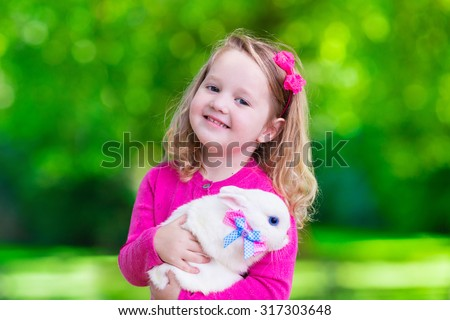 Children play with real rabbit. Laughing cute child at Easter egg hunt with white pet bunny. Little toddler girl playing with animal in the garden. Summer outdoor fun for kids with pets. - stock photo