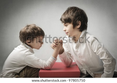 Children playing arm wrestling - stock photo