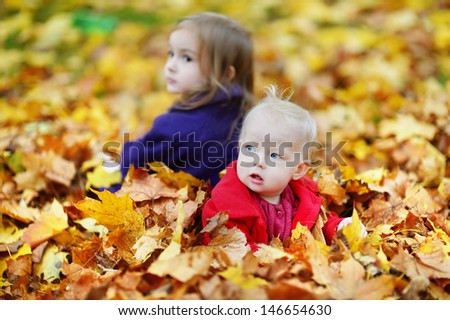 Children playing in foliage on beautiful autumn day