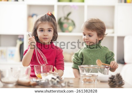 Children playing in the kitchen and learning how to bake - stock photo