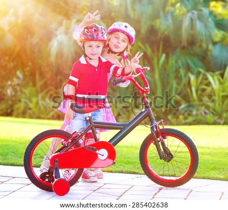 Children playing in the park, cheerful brother and sister having fun on bicycle, enjoying summer time, happy active childhood - stock photo