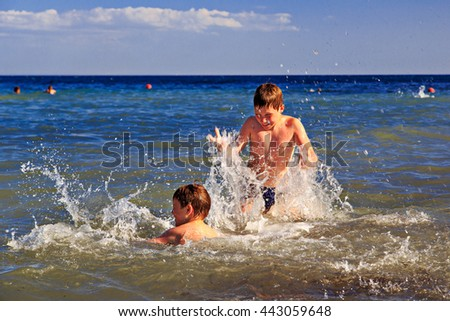 Children playing in the sea. The boys squirting water - stock photo