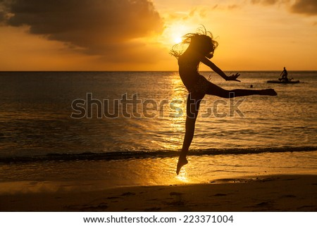children playing in the Sunset at Blue Bay Beach Curacao one of the Caribbean ABC islands - stock photo