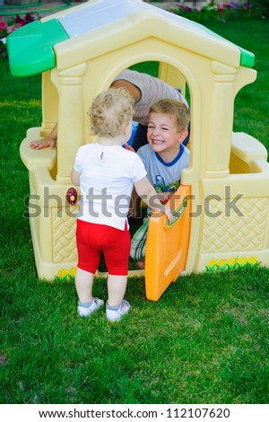 Children playing in toy house at playground - stock photo
