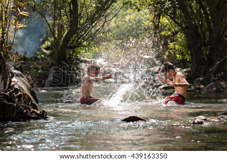 Children playing in waterfall.