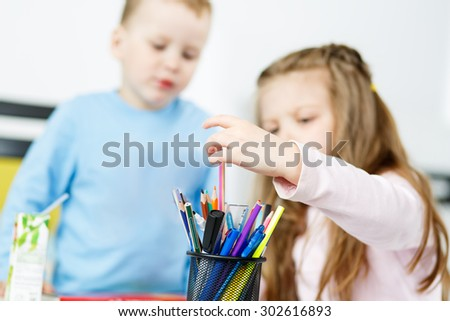 Children playing. Little boy and girl spending time together. Brother and sister drawing something with multicoloured pencils. Girl choosing suitable colour from bunch of pencils. Family concept