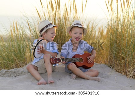 children playing music at the seaside - stock photo
