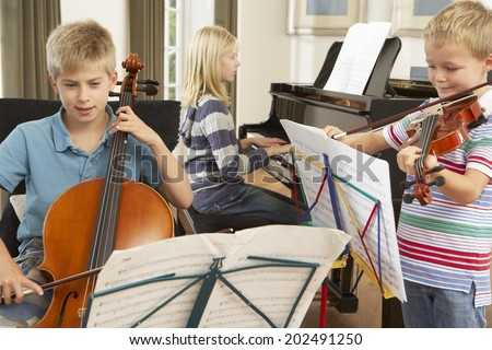 Children playing musical instruments at home - stock photo