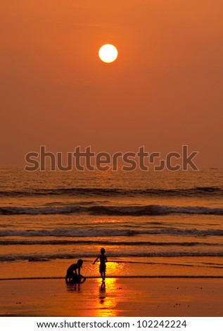 Children playing on a beach in sunset - stock photo