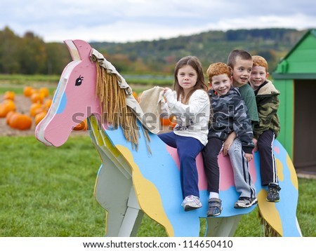 Children playing on a fake wooden horse on a pumpkin farm