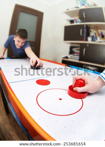 Children playing on air hockey at home - stock photo