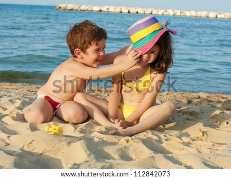 Children playing on the beach with a hat