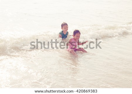 Children playing outdoors at the beach.