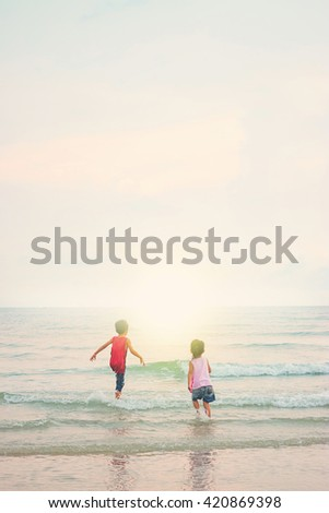 Children playing outdoors at the beach. - stock photo