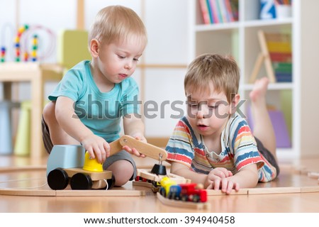 children  playing rail road and car toys in playroom - stock photo