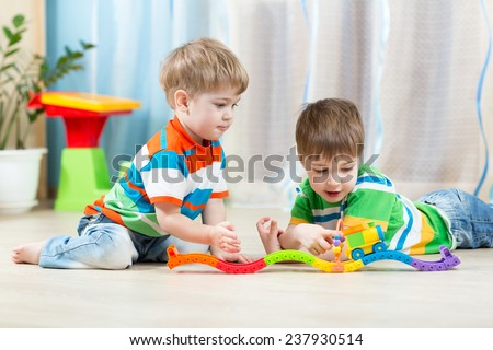 children  playing rail road toy in playroom - stock photo
