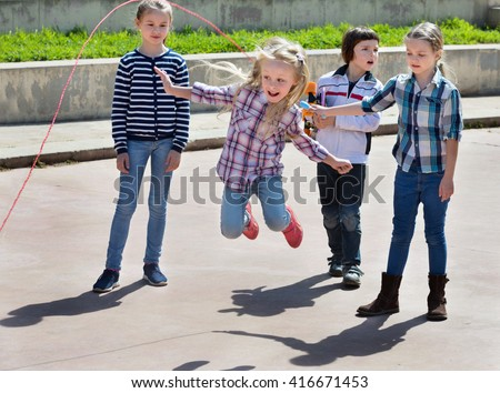 Children playing skipping rope jumping game and laughing outdoors
