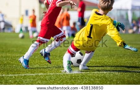 Children Playing Soccer Football Match. Youth Soccer Forward and Goalkeeper Duel. Football soccer game. Players footballers running and playing football match. Forward footballer against goalkeeper. - stock photo