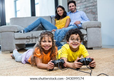 Children playing video games on the carpet in living room while parents on the sofa - stock photo