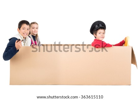 Children playing VIP people in a cardboard box limousine