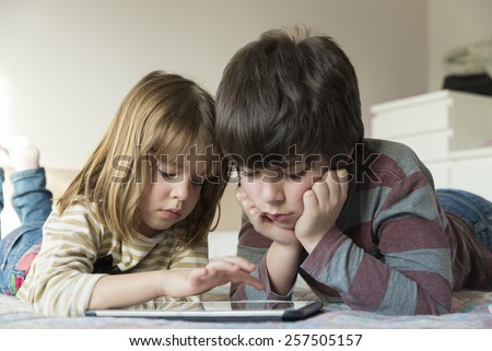 Children playing with a digital tablet on the bed