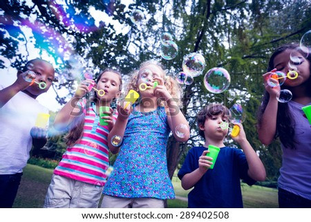 Children playing with bubble wand in the park on a sunny day - stock photo