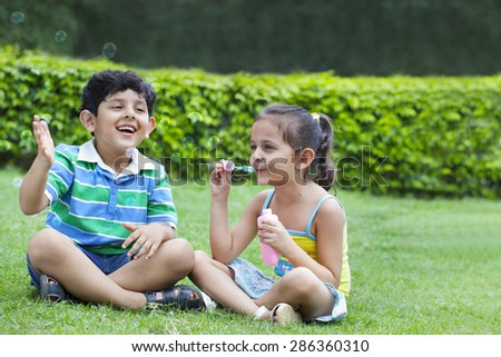 Children playing with bubbles - stock photo
