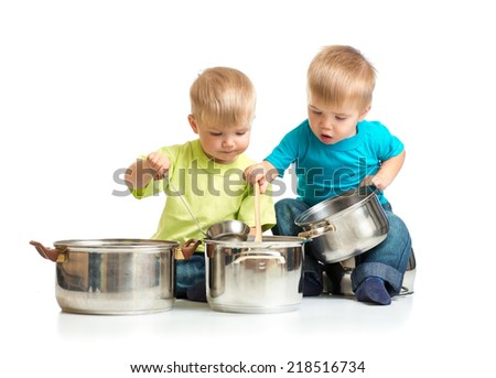 children playing with pans as they are cooking together isolated - stock photo