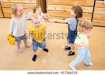 Children playing with soap bubbles in kindergarten - stock photo