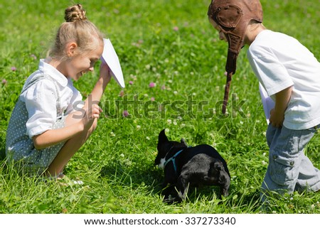 Children playing with the dog (French bulldog) in the park on the grass. Brother and sister. - stock photo