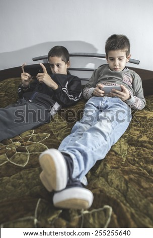 Children playing with their smartphones. Two boys with mobile phones - stock photo