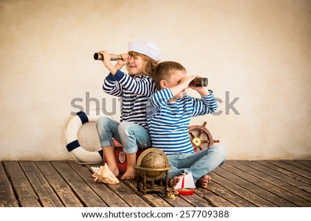 Children playing with vintage nautical things. Kids having fun at home. Travel and adventure concept. Retro toned image - stock photo
