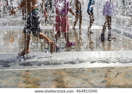 children  playing with water in park fountain. Hot summer. Happy children have fun playing in water fountains