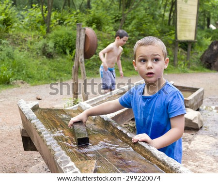 Children playing with water in wooden fountain in park or natural playground