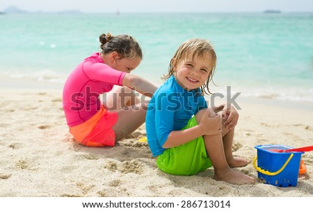 Children plays in the sand at the beach