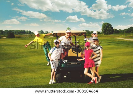 Children posing near golf car at golf course at summer day - stock photo
