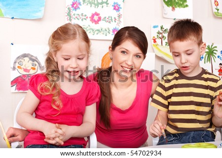 Children  preschooler with teacher in play room. - stock photo