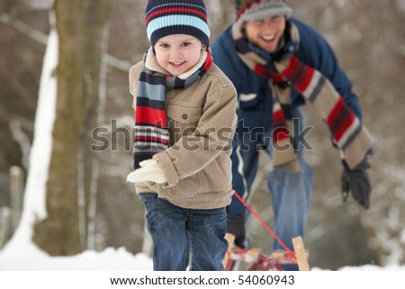 Children Pulling Sledge Through Winter Landscape - stock photo
