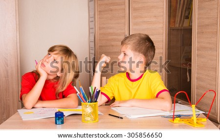 Children quarreling while doing homework together.  - stock photo