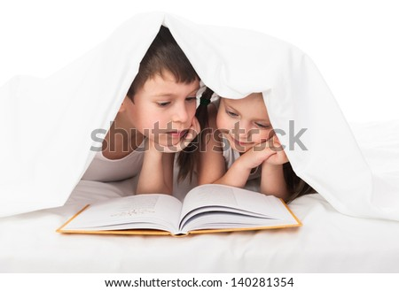 children read a book in bed under the blanket - stock photo
