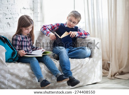 Children readind book in living room siting on the sofa - stock photo